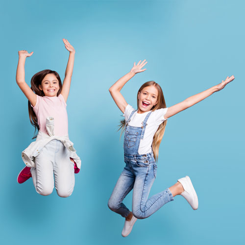 two-pre-teen-girls-jumping-in-air-laughing