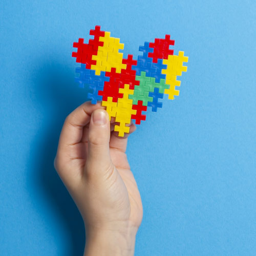 child-hand-holding-colorful-puzzle-heart-on-blue-background